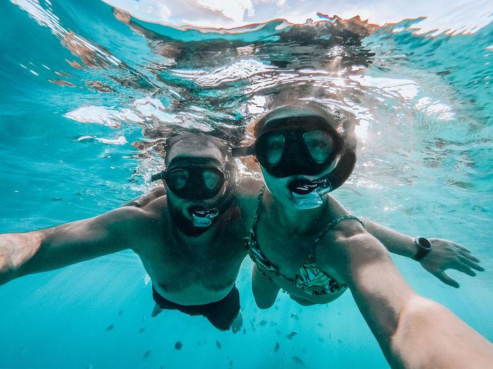 Portrait of couple snorkeling in sea