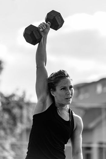 Athlete Lifting Dumbbell While Standing Outdoors
