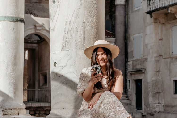 Portrait of young woman holding camera in front of building