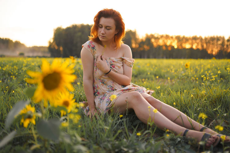 Full length of young woman sitting by yellow flowers