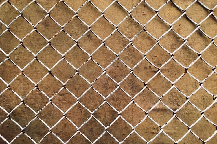 Full Frame Shot Of Chainlink Fence Against Wall