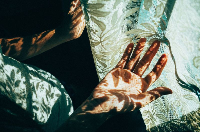 High angle view of person palm by curtain with sunlight