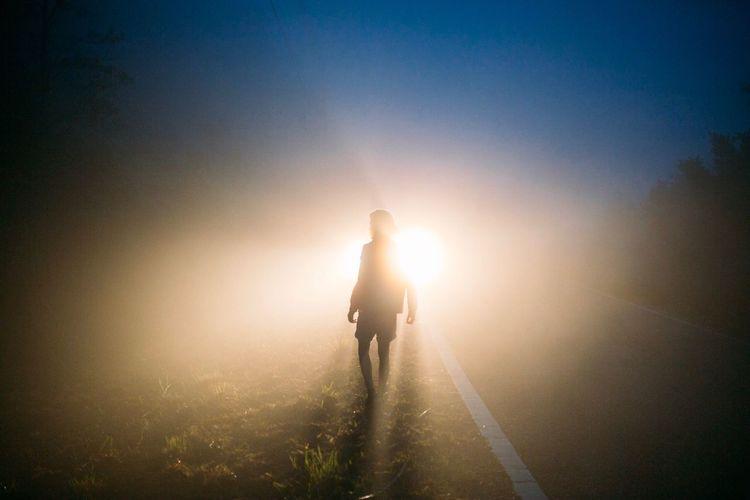 Silhouette man walking against sun during sunset