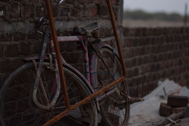 Abandoned bicycle against wall