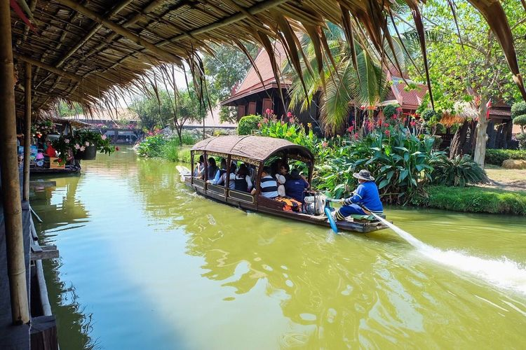 People on boat in canal along trees