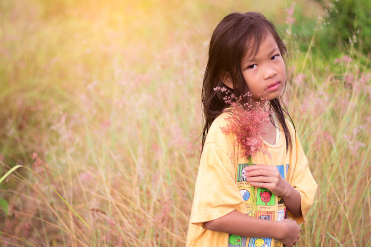 Portrait of girl holding plant while standing on grass