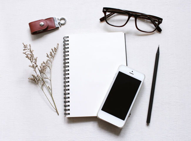 Desk Day Eyeglasses  Indoors  No People Note Papers Notebook Office Supply Smartphone Stationery Technology Top View White Background Wireless Technology Workspace