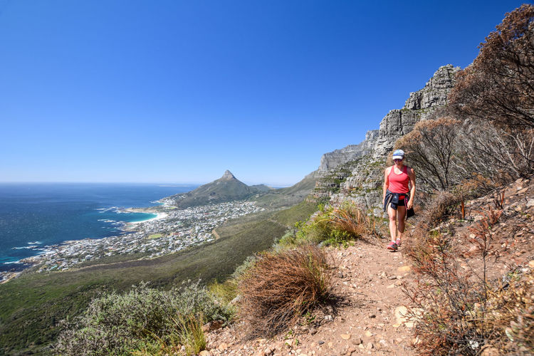 Beautiful view of the suburb of Camps Bay and Lion`s Head and Table mountain right in Cape Town, South Africa. Young female hiker at Kasteelspoort Hiking Trail, part of Table Mountain National Park. Camps Bay Cape Town Hiking Lion's Head South Africa Woman Activity Adventure Africa Climbing Healthy Lifestyle Hiker Hiking Trail Leisure Activity Lifestyles Mountain Nature One Person Outdoors Scenics Sport Table Tourism Woman Hiking Young Woman