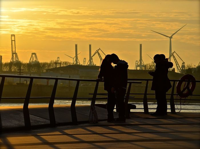 Silhouette people standing against windmill during sunset