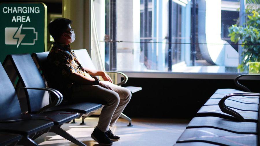 A man sitting on chair, boarding lounge t1 soekarno-hatta international airport, jakarta