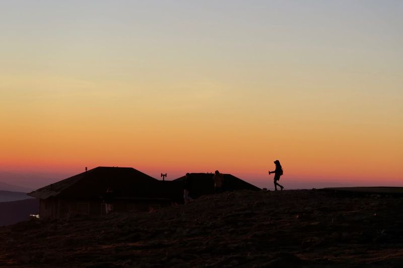 Friends walking on field against house during sunset