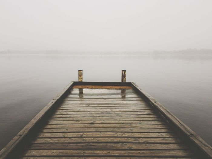 Pier over lake against sky during winter