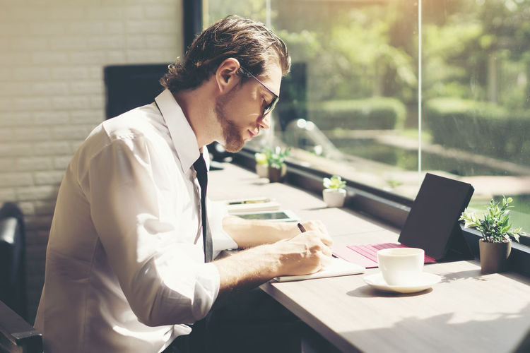 Businessman writing in book while sitting at desk in office