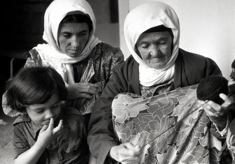 Senior woman with daughter and granddaughter knitting wool at home