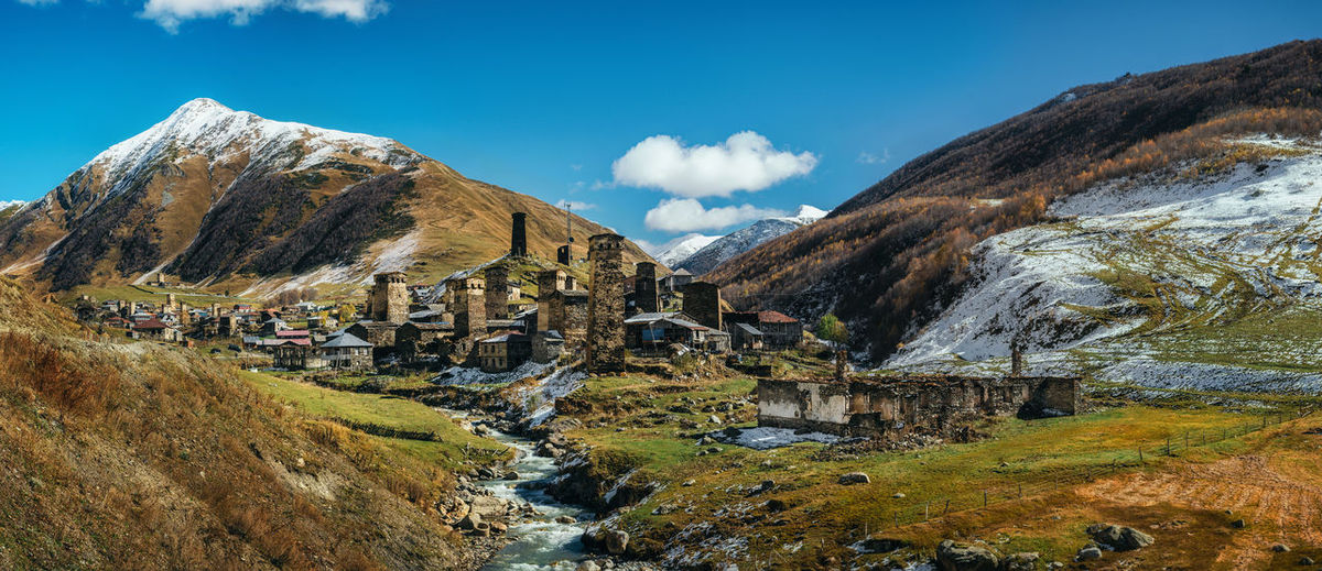 Panoramic view of Svanetian Towers in Ushguli and Inguri river in autumn. One of the highest inhabited village in Europe. Caucasus, Upper Svaneti, Georgia. UNESCO World Heritage Site. The Ushguli commune consists of Zhibiani, Chvibiani, Chajhashi and Murkmeli. Ancient Civilization Architectural Feature Beauty In Nature Cloud - Sky Georgia Georgian Architecture Highest Historical Building Houses Landscape Landscape_Collection Mountain Mountain Range Mountain Village Nature Panoramic River Svaneti Towers Travel Destinations Village Life Miles Away