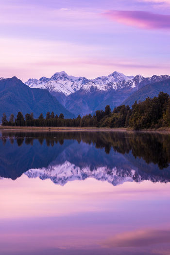 Stunning reflection of the Southern Alps in Lake Matheson at sunrise The Traveler - 2018 EyeEm Awards Travel Winter Beauty In Nature Cloud - Sky Colorful Dawn Idyllic Lake Mountain Mountain Range Nature New Zealand No People Reflection Scenics - Nature Sky Standing Water Sunrise Symmetry Tranquil Scene Tranquility Travel Destinations Water