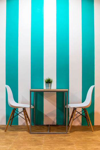 Desk,chairs & teatime in comfortable area. Background; Chair Coffee Shop; Comfortable Concept; Creative; Folding Chair Furniture Indoors  Interior; Lifestyle; Modern No People Seat Space; Style; Table Trendy; Turquoise; Vacation; Vase; White;
