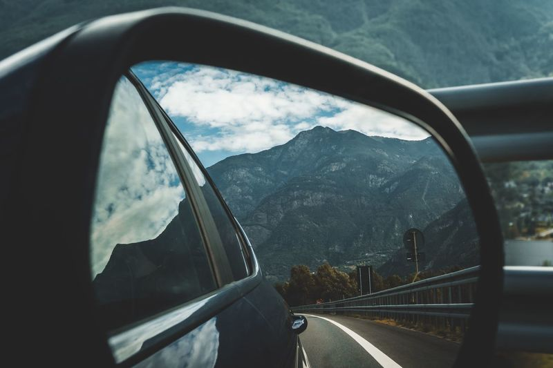 Reflection Of Mountains In Side-View Mirror Of Car