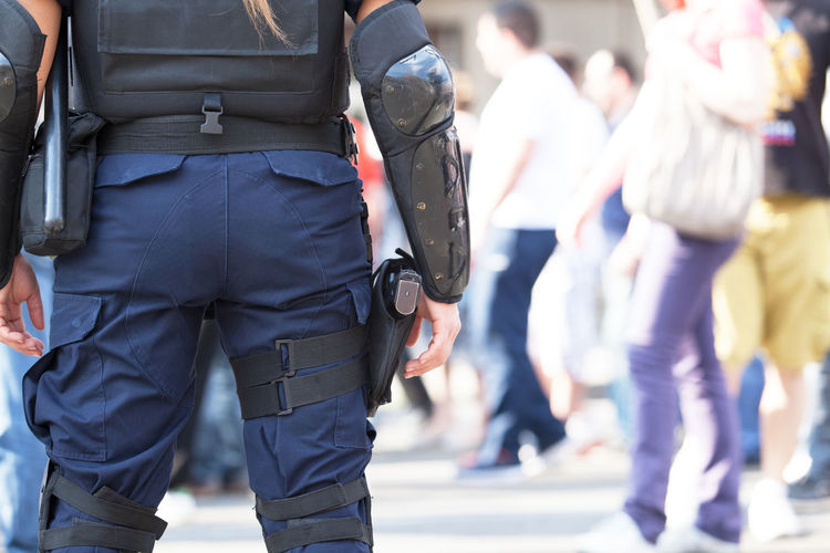Rear view midsection of female police officer standing with hand on hip