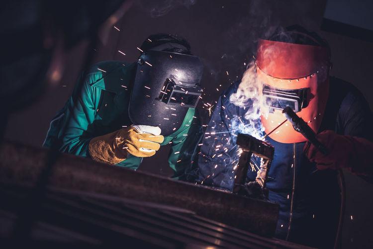Men welding in workshop