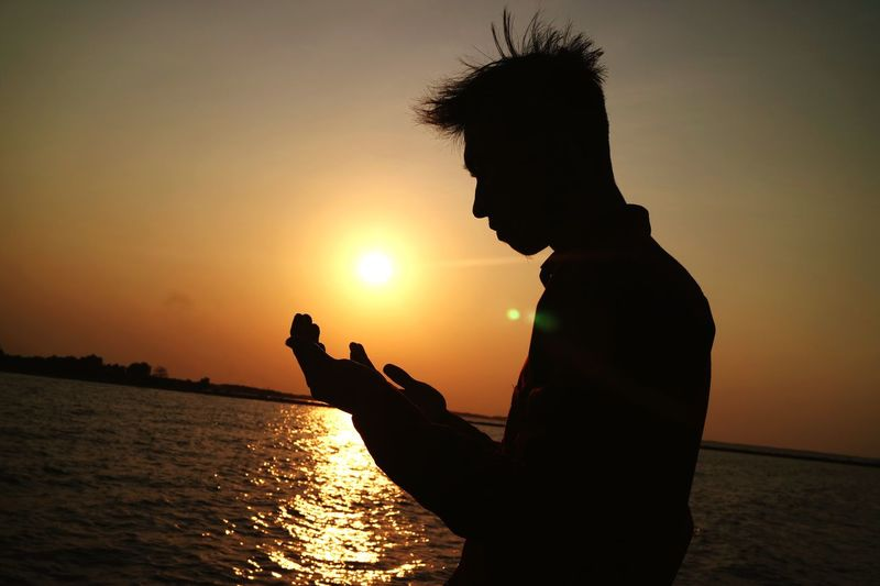 the blessing of god at sunset Sunset Silhouette Water Sky Orange Color Real People Leisure Activity Profile View Outdoors Beauty In Nature Side View Men Lifestyles Waist Up Scenics - Nature Sunlight Sea Sun Nature One Person