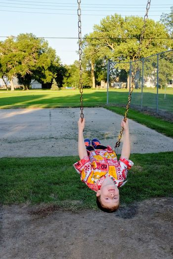 Boy swinging at playground