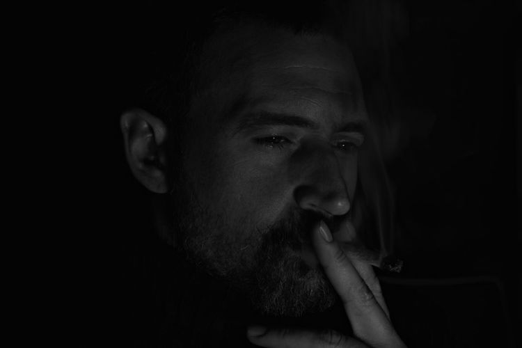 Close-Up Of Man Smoking Marijuana In Dark Against Black Background