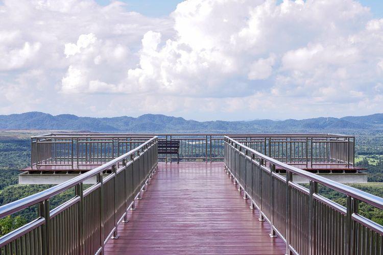 Footbridge over lake against sky