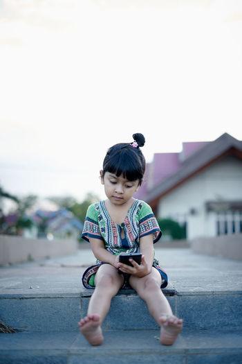 Full length of girl using phone against clear sky