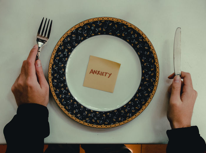 Cropped hands of person cutlery by plate with text on adhesive note over table