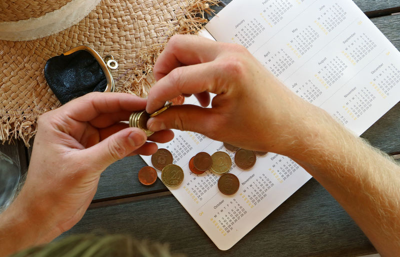 Cropped hands of man calculating money on diary