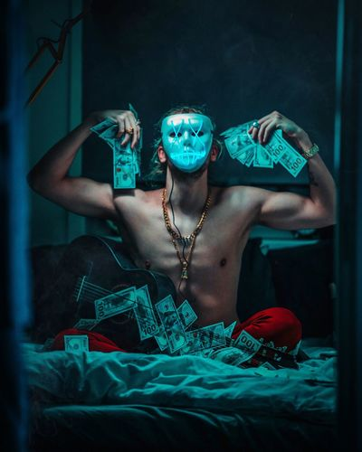 Young Man Wearing Mask While Sitting With Money And Guitar On Bed