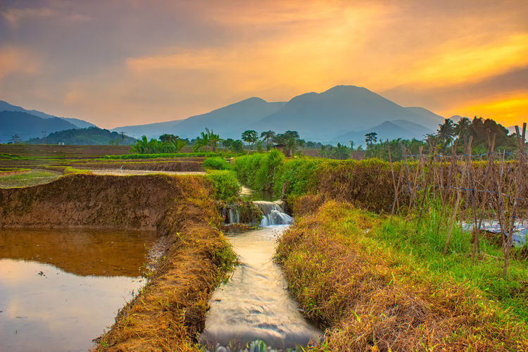 Stream flowing by river against sky during sunset