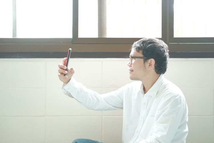 Side view of young man holding eyeglasses against wall