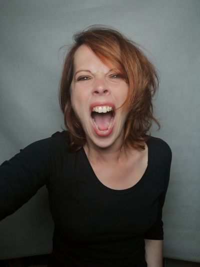 Portrait of beautiful woman shouting against wall