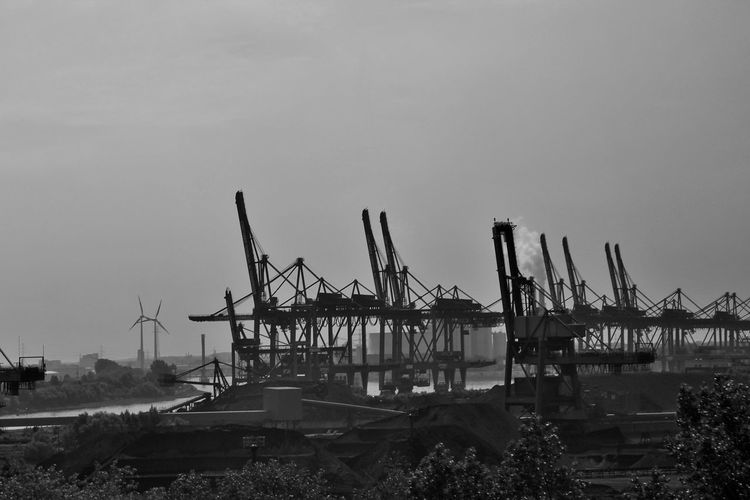 Cranes by river against sky at harbor