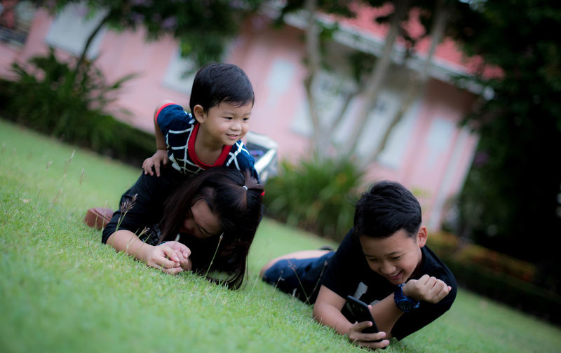 Boys holding father with baby in park