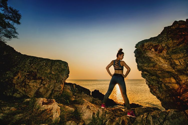 Rear view of woman standing by sea on rock during sunset