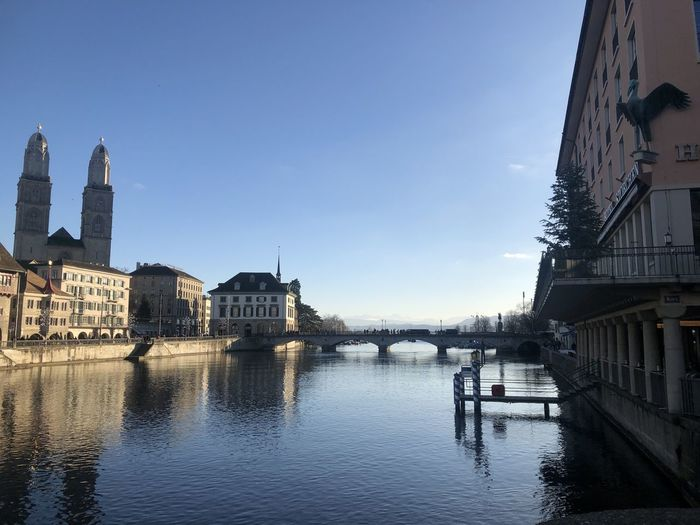 View of buildings by canal against sky in city