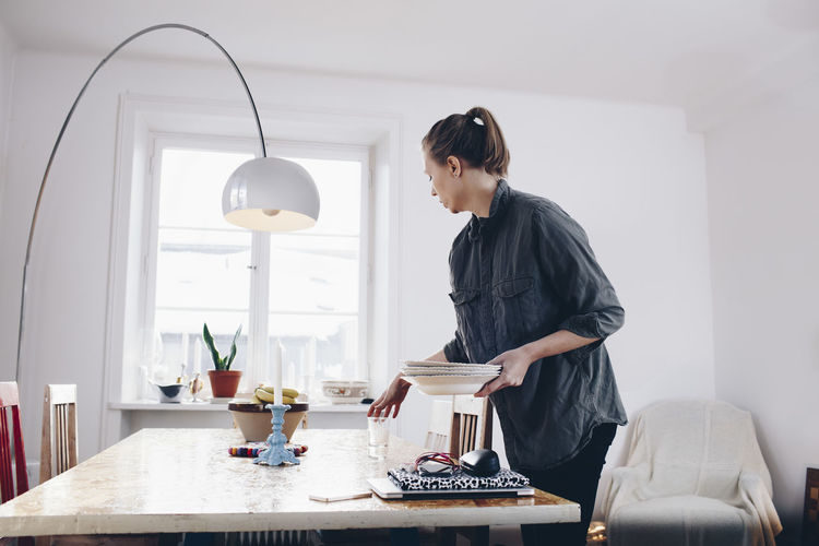 Side view of woman standing in kitchen