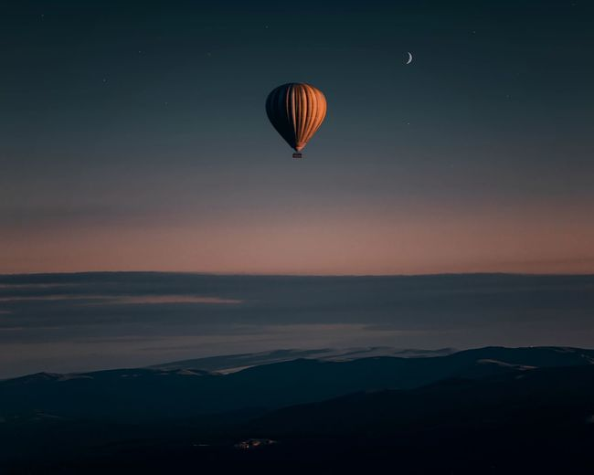Hot air balloons flying over silhouette mountain against sky during sunset
