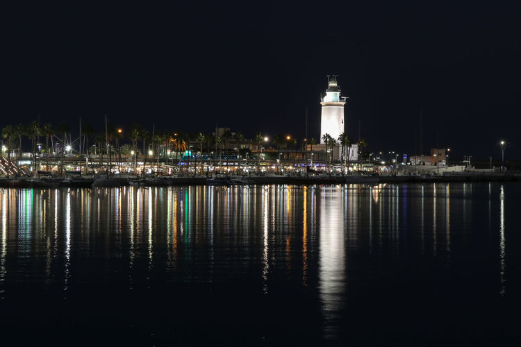 lighthouse at night Reflection Night Illuminated Architecture Building Exterior Water Built Structure Waterfront City No People Building Sky Nature Tower Outdoors Lighting Equipment Clear Sky Copy Space Glowing Nightlife Lights Lighthouse Harbor Sea Night Lights