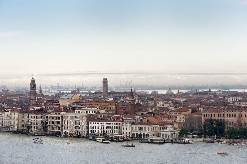 Grand canal by cityscape against sky