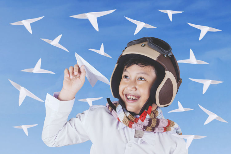 Close-up of boy playing with paper airplanes while standing against blue sky