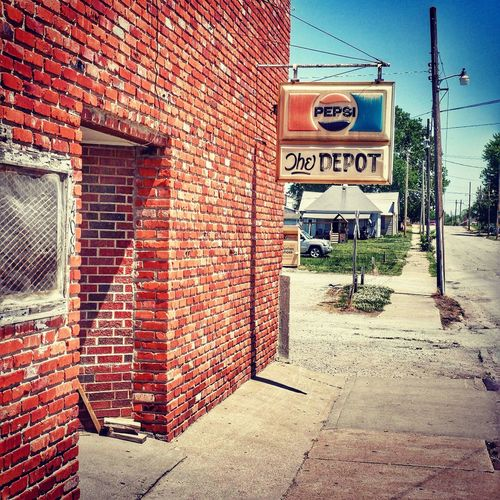 DEPOT DREAMER ~ Richmond, Missouri USA ~ Brick Wall Text Day Communication Outdoors Architecture Built Structure No People Guidance The Way Forward Building Exterior Road Sign Sky Urbanexploration Roadside America Kansascityphotographer KCACArtist Missouriphotography Walker Evans Cityscape Street Views Relicsofthepast Frozen In Time Old-fashioned Edward Hopper