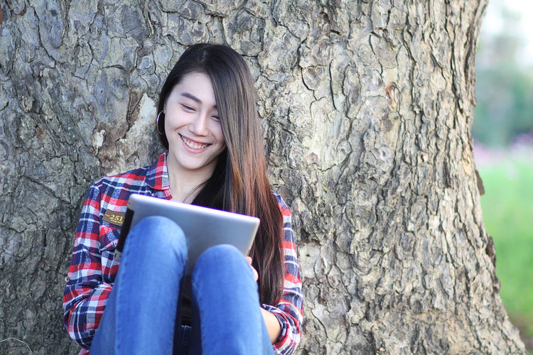 Happy beautiful woman using digital tablet sitting against tree trunk