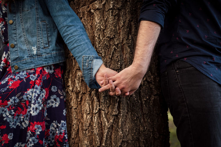 Midsection of people with holding hands against tree
