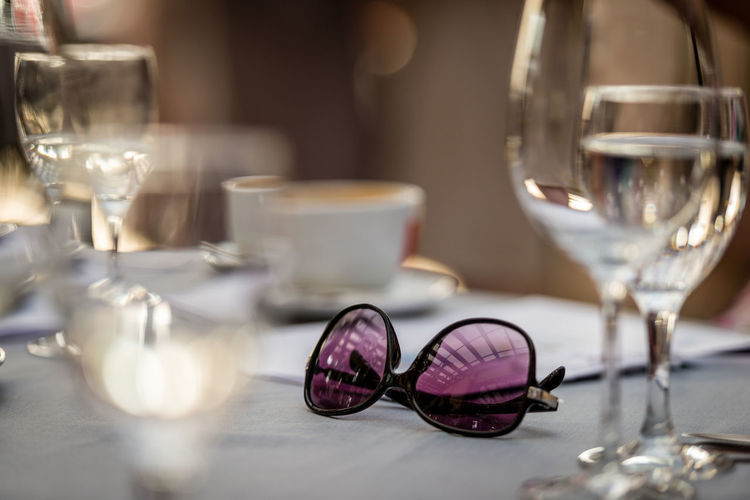 Close-up of wine glass and sunglasses on table