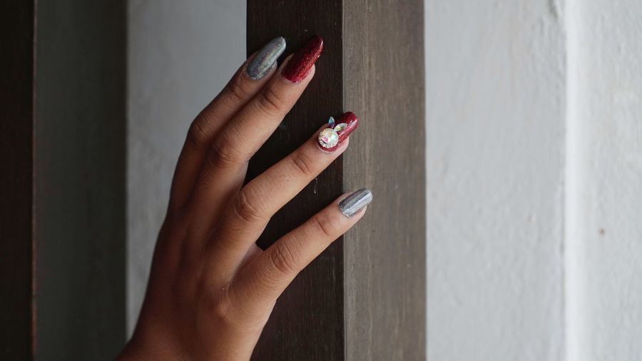 Close-up of woman hand with nail art on wall