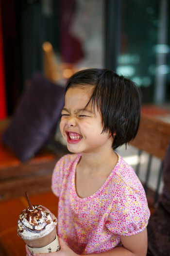 Cute girl making a face while holding ice cream